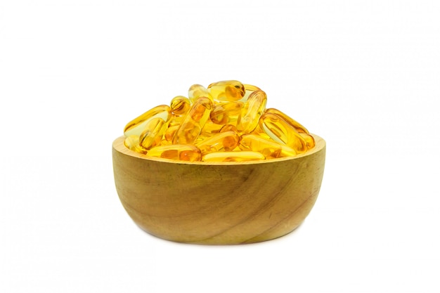 Huile de foie de morue en gélules dans une tasse en bois blanche. Photo Premium