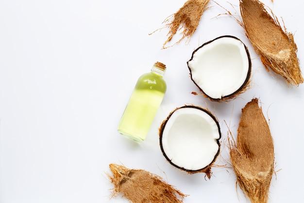 Huile de noix de coco avec des noix de coco sur blanc Photo Premium