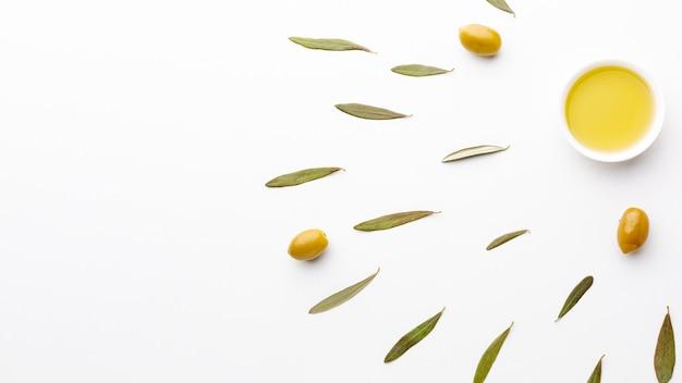 Huile d'olive dans une soucoupe avec feuilles et espace de copie Photo gratuit