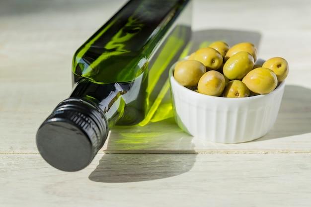 Huile D'olive Extra Vierge En Bouteille Verte Et Olives Vertes Fraîches Sur Table En Bois. Photo Premium