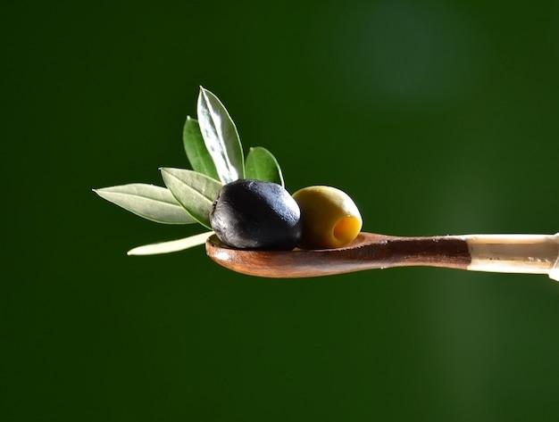 L'huile d'olive tombant sur deux olives à feuilles d'olivier pour assaisonner une salade méditerranéenne. Photo Premium