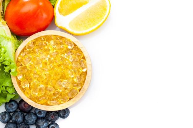 Huile de poisson, capsule molle, oméga 3, compléments alimentaires en capsules de vitamine d avec des légumes Photo Premium
