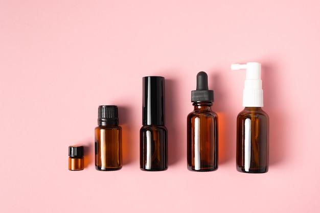 Huiles Essentielles, Diverses Bouteilles D'aromathérapie Sur Une Surface Rose. Concept D'aromathérapie Et De Parfums Photo Premium