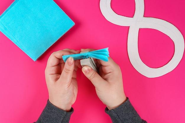 Huit bricolage en carton décoré de fleurs artificielles en papier de soie bleu fond rose. Photo Premium