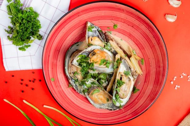 Huîtres dans une assiette garnie d'herbes Photo gratuit