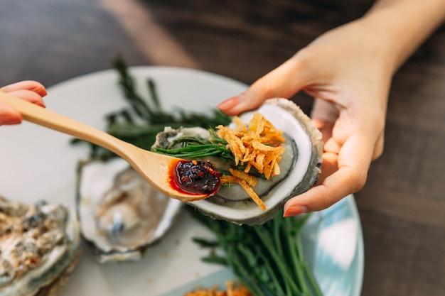 Huîtres fraîches dans une coquille à la main, nappées d'échalotes frites, de pâte de chili, d'acacia pennata et d'une sauce de fruits de mer à la thaïlandaise. Photo Premium