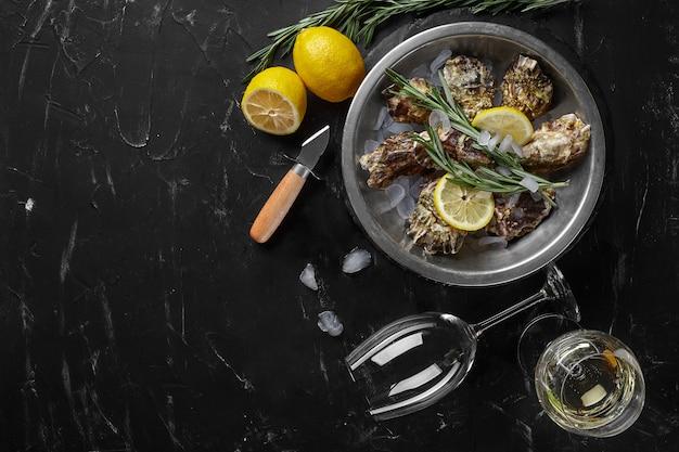 Huîtres Fraîches Fermées, Glace, Citron Sur Une Plaque Métallique Ronde Photo Premium