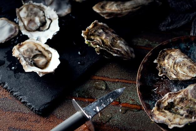 Huîtres fraîches ouvertes sur un fond sombre, un couteau et des gouttes d'eau. style rostik. Photo Premium