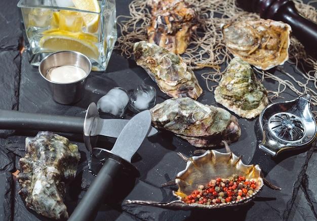 Huîtres sur plaque de pierre avec glace, citron, filet de pêche, poivre et couteau. Photo Premium