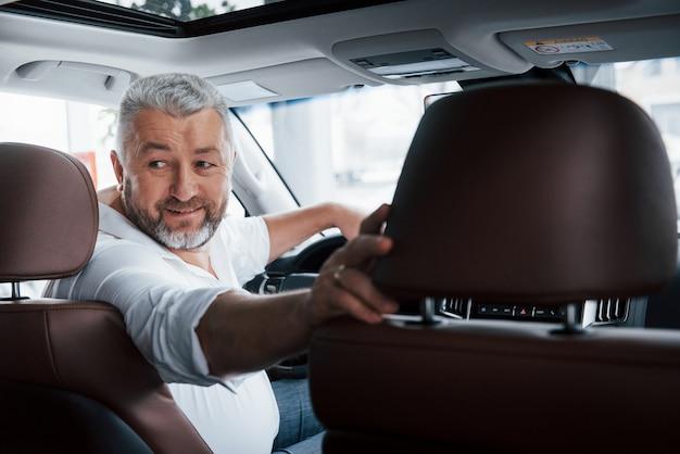 Humeur Joyeuse. Conduire Une Voiture En Marche Arrière. Regardant Derrière. Homme Dans Sa Toute Nouvelle Automobile Photo gratuit