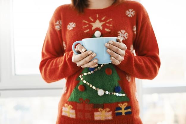L'humeur De Noël Est Dans L'air. Photo Recadrée D'une Femme à La Maison, Portant Un Drôle De Chandail De Noël Avec Un Arbre, Tenant Une énorme Tasse De Café Et Debout Sur La Fenêtre, Se Sentant à L'aise Photo gratuit