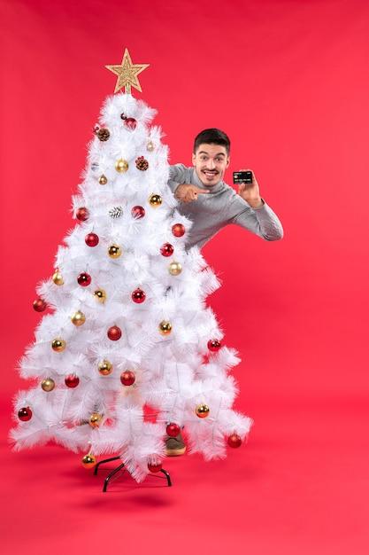 L'humeur De Noël Avec Un Gars émotionnel Debout Derrière L'arbre De Noël Décoré Et Prenant Le Téléphone Photo gratuit