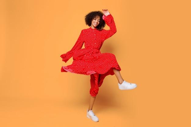 Humeur Rêveuse. élégante Fille Africaine Dansant Et Sautant Sur Orange Photo gratuit