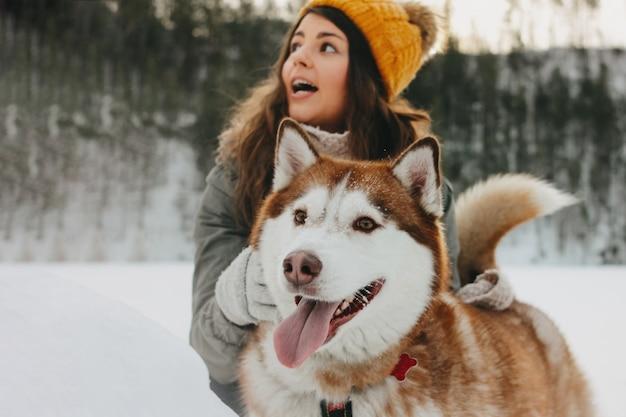 Husky chien rouge avec sa maîtresse fille brune en forêt en plein air en saison froide Photo Premium