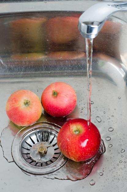 Hygiène Alimentaire. Trois Pommes Rouges Dans Un évier En Métal Sous Un Jet D'eau. Photo Verticale Photo Premium