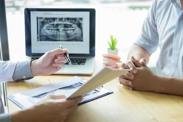 Hygiéniste dentaire montrant et montrant une mâchoire factice à un patient qui mâche ou guérit des dents. Photo Premium
