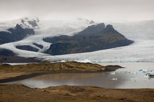 Icebergs bleus congelés dans un lac glaciaire Photo Premium