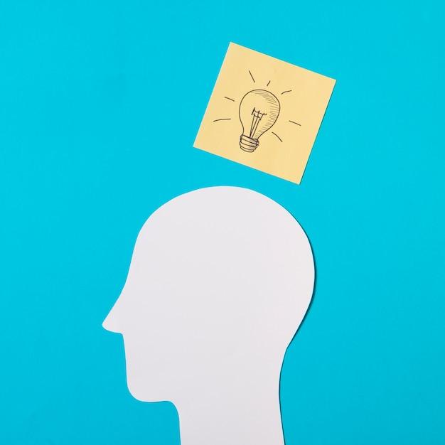 Icône d'ampoule dessiné sur note autocollante sur le papier découpé tête sur fond bleu Photo gratuit