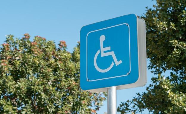 Icône handicapée sur le sol de la réserve de stationnement pour personnes handicapées dans une station d'essence urbaine Photo Premium