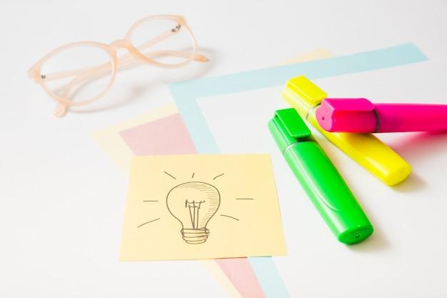 Icône d'idée sur une note adhésive avec marqueur de surbrillance; lunettes et papiers cartonnés Photo gratuit