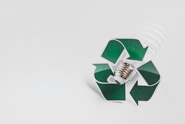 Icône de recyclage sur ampoule fluorescente compacte sur fond blanc Photo gratuit