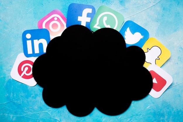 Icônes d'application mobile vives disposées autour de nuage de papier noir Photo gratuit