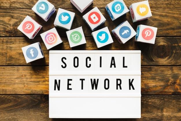 Icônes de réseautage bien connus près de texte de réseau social sur une table en bois Photo gratuit