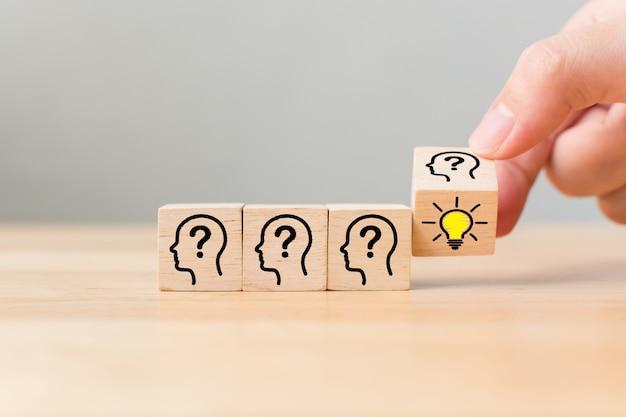 Idée créative de concept et innovation. main retourner sur un bloc de cube en bois Photo Premium