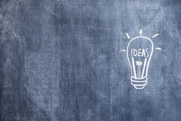 Idée éclairée dessiné ampoule dessiné à la craie sur tableau noir Photo gratuit