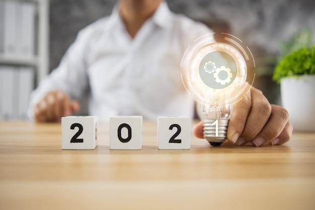 Idée Et Planification D'entreprise En Concept 2021, Homme D'affaires Tenant Une Ampoule Du Plan D'innovation Avec Un Cube De Nombre Sur Une Table En Bois Photo Premium
