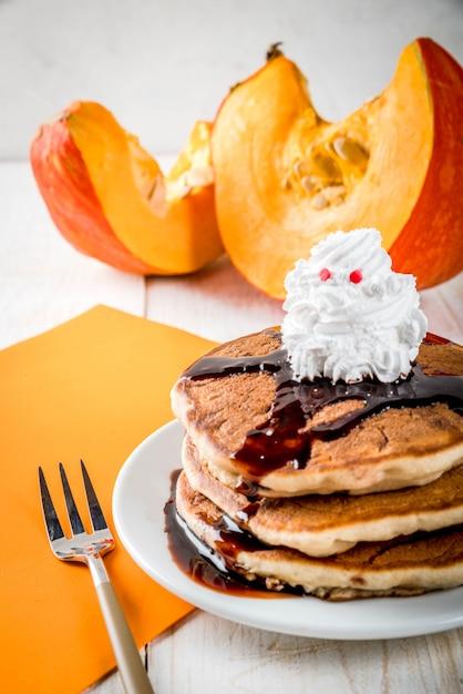 Idées Pour Le Petit-déjeuner Des Enfants, Des Friandises Pour Thanksgiving Et Halloween. Crêpes à La Sauce Au Chocolat Et Crème Fouettée En Forme De Fantôme. Sur Une Table En Bois Blanc, Copyspace Photo Premium