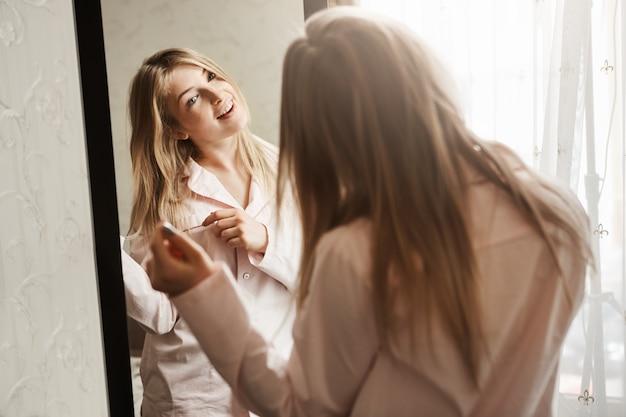 Il Est Temps De Se Déguiser Et De Partir à La Rencontre Des Aventures. Home Shot Of Beautiful Blond Caucasian Girl Looking In Mirror, Portant Des Vêtements De Nuit Et Toucher La Mèche De Cheveux, Penser à Une Nouvelle Coiffure Photo gratuit