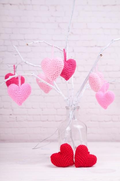 Il y a beaucoup de coeurs tricotés roses sur des branches blanches. bouteille en verre. la saint valentin. Photo Premium