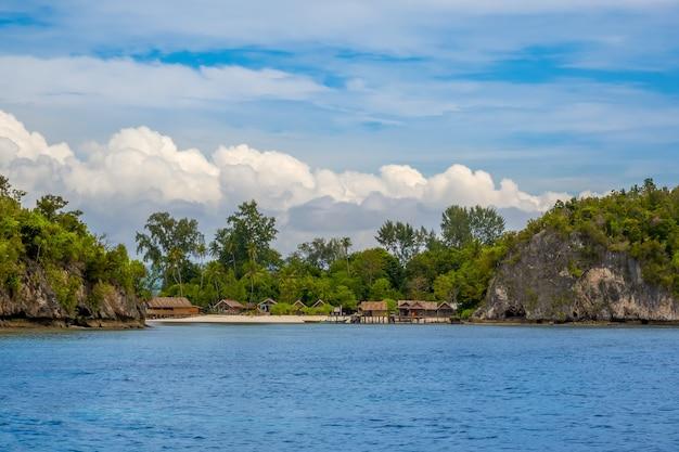 Île En Indonésie. Raja Ampat. Plusieurs Cabanes Traditionnelles Sur Le Rivage Entre Les Rochers Et La Plage Photo Premium