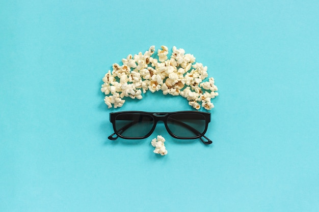 Image abstraite de spectateur, lunettes 3d et pop-corn sur fond bleu. Photo Premium