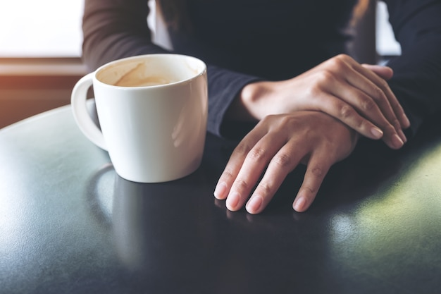 Image Agrandi D'une Femme Tenant La Main Et Boire Du Café Chaud Au Café Photo Premium