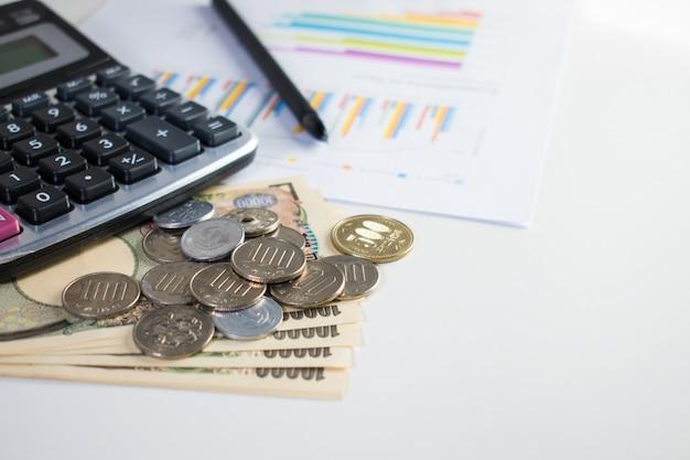 Image de banque de 10 000 yens et nombreuses pièces de monnaie avec calculatrice, stylo et papier Photo Premium