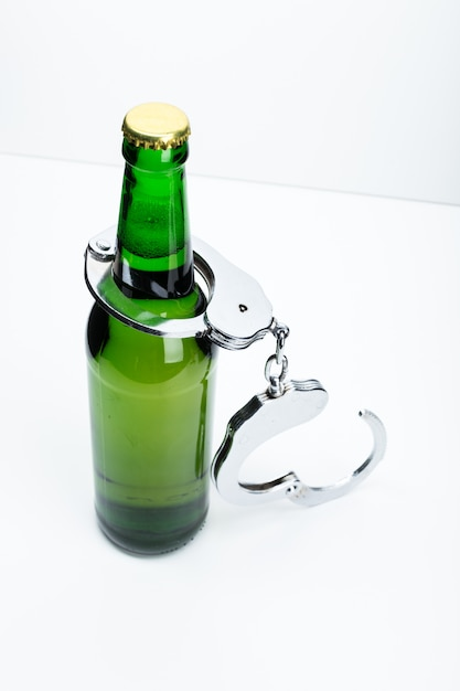 Image concept de boire illégalement mettant en vedette une bouteille de bière et une paire de menottes Photo Premium