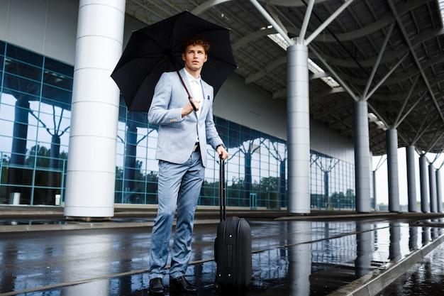 Image - Confiant, Jeune, Rousse, Homme Affaires, Tenue, Noir, Parapluie, Valise, Pluie, Terminal Photo gratuit