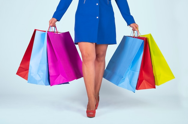 Image En Coupe D'une Femme Dans Une Robe Bleue Et Des Chaussures Rouges, Tenant Des Sacs Colorés Isolés Sur Un Fond Bleu Clair. Photo Premium
