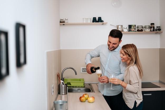 Image de couple heureux avec des verres de vin, verser le vin. Photo Premium