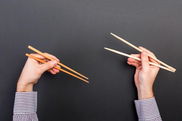 Image créative de baguettes en bois dans deux mains mâles sur fond noir Photo Premium