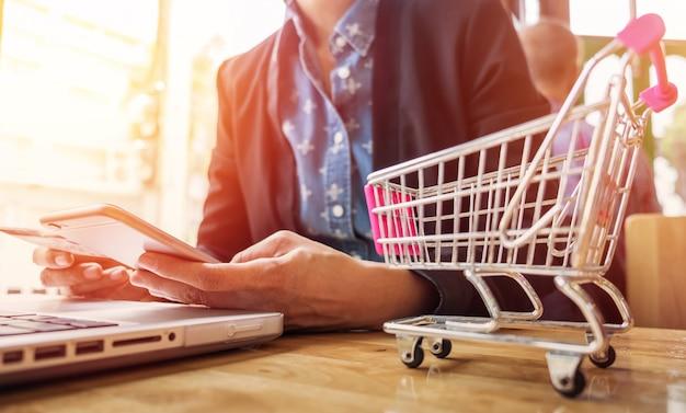 Image découpée de la femme fournissant des informations sur la carte et la clé du téléphone ou de l'ordinateur portable tout en achetant en ligne. Photo gratuit
