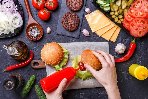 L'image Sur Deux Hamburgers Et Des Mains Humaines Ajoute Le Ketchup Dans Le Hamburger Photo Premium