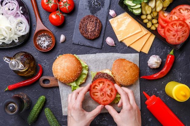 Image Sur Deux Hamburgers, Des Mains Humaines Et Des Ingrédients Photo Premium