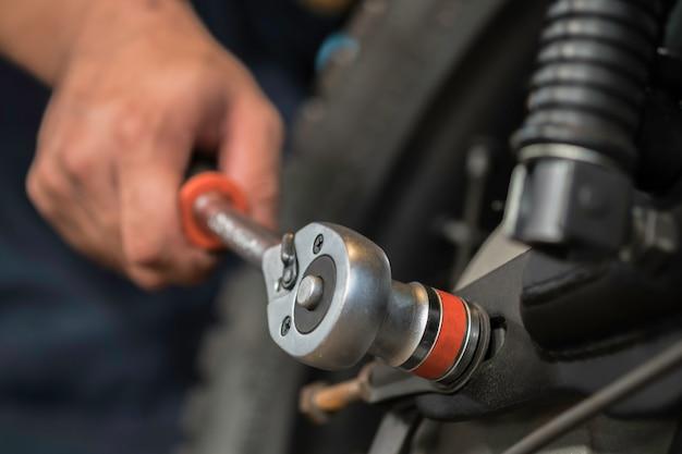 L'image est en gros plan, les gens réparent une moto utilisez une clé et un tournevis pour travailler. Photo Premium