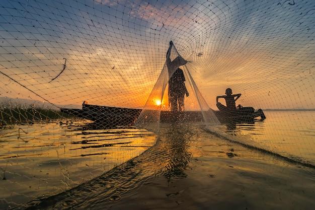 L'image est la silhouette. les pêcheurs qui pêchent commencent à pêcher tôt le matin avec des bateaux en bois. Photo Premium