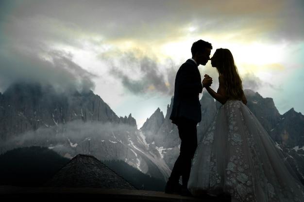 Image floue de baiser couple de mariage debout devant le magnifique paysage de montagne Photo gratuit