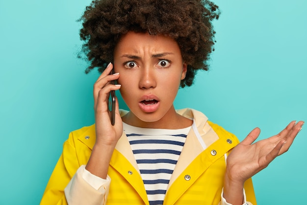 Image De Gestes De Femme Afro-américaine Frustrés Avec Paume Pendant La Conversation Téléphonique, Regarde Avec Indignation, Vêtu D'un Imperméable Imperméable, Isolé Sur Bleu, Exprime L'aversion Photo gratuit
