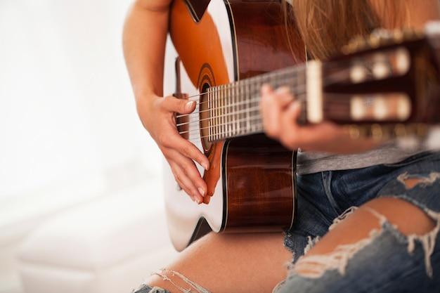 Image gros plan de la guitare dans les mains de la femme Photo gratuit